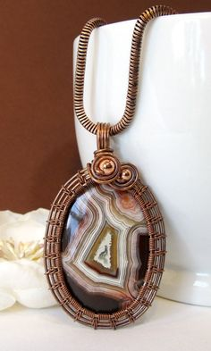 In this wire wrapped pendant, oxidized copper wire weaving frames a lovely piece of red and white banded laguna agate. I added a few beads for just a bit of extra flourish, but over all, this piece is simple and leaves the face of the beautiful stone visible. Be sure to check out the other wire wrapped agate pendants in my shop too!  This one-of-a-kind wire wrapped pendant measures approximately 2.2 long by 1.3 wide. The chain option with this is the pictured antiqued copper-plated brass…