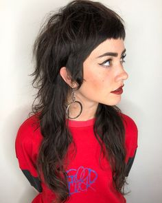 This modern mullet is totally hip and trendier than ever. We love the all over messy texture, the sideburns, and the fringe! The face framing sideburns and fringe would make this cut look super cute with an effortless updo or braids, as well. See tips to get this Messy Wavy Textured Shaggy Brunette Mullet with Micro Bangs and Sideburns and other long hairstyles, Summer to Fall haircuts, shag cuts, and hair color ideas at Hairstyleology.com.