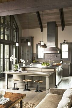 Rustic meets modern kitchen. The open kitchen features an earthy palette of muted grays and browns, natural accents, warm wooden tones, but sophisticated finishes like stainless steel appliances and marble style counter tops. French doors open to screened porch with stone fireplace.