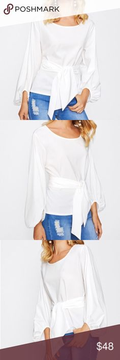 """JUST IN! Lantern sleeve tie-front blouse Lantern sleeve wrap tops are all the rage this season! This beautiful, versatile white top has it all — the full-length, feminine lantern sleeves with elastic cuffs; a slim, tapered fit to accent your figure; a perfect wrap-around sash; and a flattering, round neckline. Poly/cotton blend. Hand wash or dry clean. Runs small! Large measurements are is 17"""" shoulders, 45"""" bust, 23"""" length, 18"""" sleeves. Tops Blouses"""