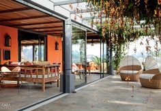 A varanda tem cobertura de madeira e vidro. Os móveis desse ambiente vieram da loja Olhar o Brasil.