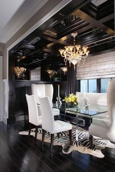 The ornate black tray ceiling is the star of this dining room, featuring white chairs, a black built-in sideboard, a zebra rug & an impressive chandelier. Proof that a black room can be divine. x