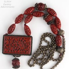 This necklace is newly assembled from old Chinese cinnabar components. The buckle and beads date to from early to mid 20th century. These beads are hand carved lacquer over wood and done with wonderful detail and clarity not found in today's cinnabar beads, which are for the most part plastic and molded rather than carved. The buckle pendant is especially beautifully deep carved and is stamped China on the back. The metal on the buckle bead caps and chain are silver over copper. The ...