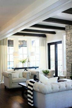 Farmhouse chic living room with fireplace; nailhead arm chairs and sofa, sofa table against window with lamps, black French door, black beamed ceiling.