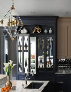 A display shelf is fixed above black mirrored refrigerator doors complementing black freezer drawers finished with satin nickel pulls.