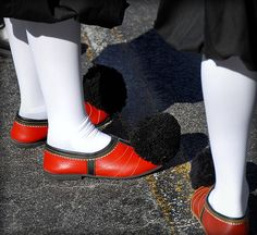 """The ""tsarouhi"" is a shoe with a history which begins during the time of Homer and extends to the period of the Ottoman Occupation of Greece (1453-1821). From 1821 onwards, the ""tsarouhi"" was established as part of the official Greek national costume and a symbol of the War of Independence. Today, the ""tsarouhi"" is worn by the Presidential Guard (Evzones), and Guards of the Tomb of the Unknown Soldier located in front of the Hellenic Parliament. ""Tsarouhia"" are completely hand-made from…"