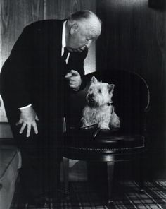 Alfred Hitchcock gives direction to his Sealyham terrier Sarah.