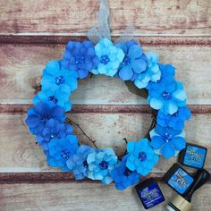 """A 8"""" grapevine wreath decorated with paper flowers. The flowers are in tones of blues and the petals have two tone inked distressing giving the petals texture. In the center of the flowers is a blue holographic flower sequin with a bead center that holders the taped floral wire. The wreath is hung on a light blue taffeta ribbon. Since these wreaths are paper it is recommended for indoor use only! They make a precious gift or use to decorate your home!"""