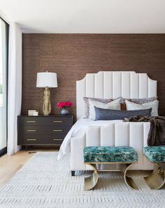 A guest bedroom displays such 1970s-inspired details as a custom fluted headboard, gold hardware, and Malachite-like bench cushions | archdigest.com