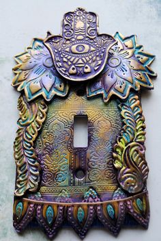 This Purple Hamsa light switch cover has a lot going on. A lot of color and texture. This switch plate is made from layers of purple polymer clay