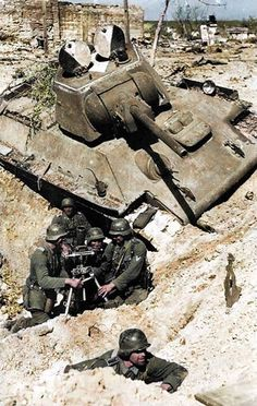 A German mortar team operating an 8 cm. Granatwerfer 34 close to a 'knocked out' T-34/76 Soviet tank near Stalingrad. c. September 1942 (Colourised by Royston Leonard UK)