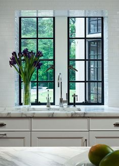 All white kitchen with black steel windows, dorenbracht faucet and spray and white subway tile