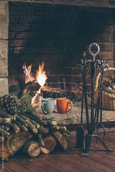 Fireplace in a comfortable home. Woodpile, basket of pine cones and two hot cups. By BONNINSTUDIOAvailable to license exclusively at Stocksy...