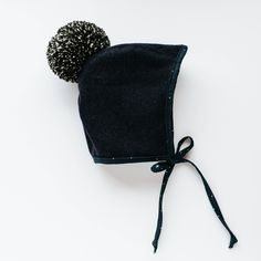 Almost black purple blue Melton wool trimmed with starry night cotton. Topped with a hand ruffed Pom. Lined with 100% cotton. With the option of a Merino wool lining for with the Brimless bonnet for extra warmth.   Melton wool is a natural water repellent.   • All garments are made to order, by h