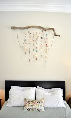 wall hanging made from strands of beads, seashells and chandelier prisms, hanging from a driftwood branch.