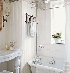 Install vintage-inspired plumbing. Merge modern and traditional in a bath by combining a new sink and beaded board with an old claw-foot tub and faucets that have a period feel. An all-white palette looks fresh, while a handheld faucet adds vintage charm to this renovated room.