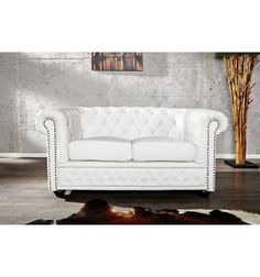 Un canapé design 2 places Chesterfield blanc pour un pur moment de détente. en simili cuir antique coloris blanc, les boutons décorée et fixé par des clous d...