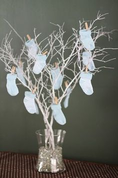 Use mini clothespins to pin baby socks to a twig centerpiece. Adorable for a winter baby shower! #BabyShower