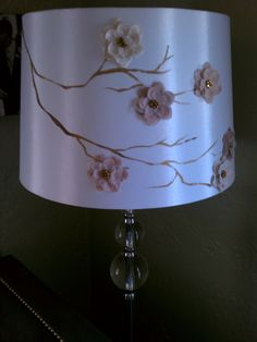 Paint branches on a plain lampshade with craft paint and glue on fabric flowers.