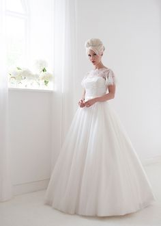 Penelope  A pretty floor length full skirted tulle gown with lace bodice and floaty sleeves  A semi sweetheart bodice with lace overlay and floaty lace sleves. The back has a plunging V for a show stopping look. Dress has no train for easy movement