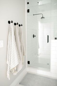 Oil rubbed bronze towel hooks are mounted to a light gray wall over a gray bath . Oil rubbed bronze towel hooks are mounted to a light gray wall over a gray bath mat placed on white hex floor tiles outside of a seamless glass shower. Bathroom Renos, Bathroom Towels, Bathroom Renovations, Bathroom Interior, Modern Bathroom, White Bathroom, Bathroom Ideas, Hooks In Bathroom, Bathroom Towel Hanger