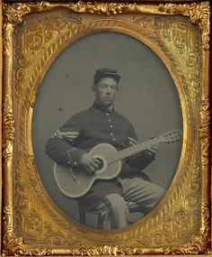 ca. 1861-65, [tintype portrait of  Edwin Chamberlain, non-commissioned Union Officer, holding his guitar]   Accompanying the tintype is a piece of paper stating his familial reliations and his death during the Civil War.   via Heritage Auctions