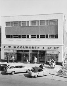 FWW01/01/1078/001 Exterior view of the front elevation of F W Woolworth and Company Limited, 24 The Broadway, with cars parked outside and groups of people on the pavement