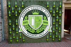 "Bottles and a crest emblazoned with ""members only"" decorated a press wall. Turf covered the backdrop, and glowing Svedka..."
