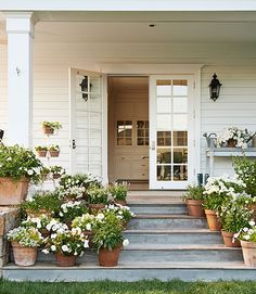 """Natural light also floods in through the French doors along the wraparound porch, and """"everywhere you go, you can see the garden,"""" Blazona says. In this photo: White flowers—including salvia, violas, petunias, begonias, and lantana—adorn the side porch. Jann Blazona California Garden - Farmhouse Decorating and Garden Ideas - Country Living"""
