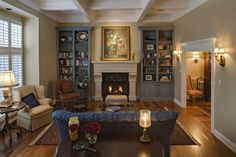 Lush details and variety of tone abound in this beautiful living room, featuring a detailed white ceiling over beige walls and a rich hardwood floor. A pair of grey full height bookshelves flank the central stone fireplace, while an array of chairs in blue, tan, and red, respectively, circle a patterned area rug with mirror topped coffee table.