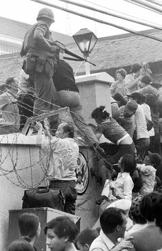 In this April 29, 1975 file photo, people try to scale the 14-foot wall of the U.S. Embassy in Saigon, trying to reach evacuation helicopters, as the last of the Americans depart from Vietnam.  The Vietnam War ended on April 30, 1975.