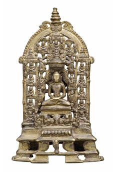 A GILT BRONZE JAIN TIRTHANKARA, PROBABLY GUJARATA, POSSIBLY 15TH/16TH CENTURY OR EARLIER  the central figure  surrounded by fourteen figures seated in meditation, with numerous other figures, the central Tirthankara seated in dhyanasana on a throne supported by two adorsed lions and flanked by figures with inscription to the reverse, side and front,    21.5cm high