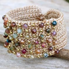 A beautiful boho chic wristband bracelet with crocheted brass beads and agates dyed in many colors with khaki threads, adding labradorite buttons to fasten the bracelet at one of two lengths. Product