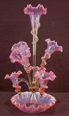 Victorian pink iridescentart glass epergne, has 6 trumpets, 23in. T, 11in. Dia., ca. 1880.