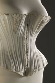 Corset, made of one layer of white twill-weave cotton and stiffened with 30 strips of whalebone slipped into the vertical channels. The two triangular panels beneath the bust and the edges where the corset hooks together are decorated with pink silk machine embroidery. The corset is laced here to a waist measurement of 66 cm, or 26 inches. This corset dates from about 1870 to 1875. - Fashion Museum - Bath