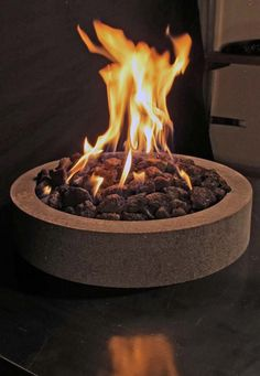 Limited edition square reclaimed steel fire table with natural Lava Stone fire pit area for burning propane or natural gas.  Standard 20lb propane tank fits under table.