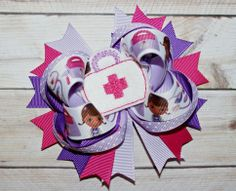 """This listing is for a super cute Doc McStuffins themed hair bow. The bow features a fun printed ribbon with coordinating solid ribbons. The bow is finished with a felt centerpiece. This bow measures about 5"""" and can be mounted on an alligator clip or a french barrette. All ribbon ends are heat se..."""