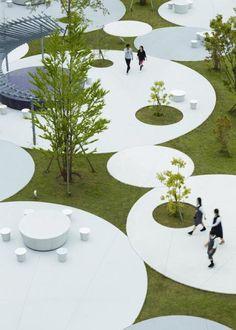 工場建築に囲まれた中でこの広場には角を作らず、すべてを円形で統一したデザインとし、社員が自然に親しみ、集まれるような場づくりを目指している。それは企業理念である『