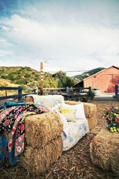 A couch from hay bales, quilt over it.