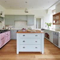 Coordinating kitchen islands and solid wood kitchen cabinets painted in Farrow & Ball's Mizzle create a harmonious kitchen vibe.