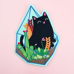 "One of the prettiest patches I have ever seen! Cute cat peeking out of a terrarium full of succulents.  By Natelle Draws StuffLarge size perfect as a centre piece on the back of your jacket6"" (152.4 mm) tall embroidered patch on felt backing, iron-on"