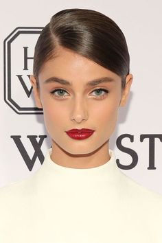 """Who: Taylor Hill What: Evening Glamour How-To: Makeup artist Hung Vanngo and hairstylist Seiji Yamada turned the new model into a """"modern-day Audrey Hepburn"""" for the amfAR gala, giving her a sleek deep part, full brows and patent-red lips. Editor's Pick: Hourglass Opaque Rouge Liquid Lipstick in Icon, $28, sephora.com."""