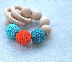 Teething toy with crochet teal, cyan/aqua, bright orange wooden beads and 2 wooden rings. Wooden rattle. Teething ring on Etsy, $18.00