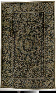 anoniem | Savonnerie-tapijt met bloem- en acanthuspatroon, attributed to Manufacture de la Savonnerie, c. 1650 | Savonnerie-tapijt met bloem- en acanthus-patroon. Op een blauw-zwart fond staat een tweezijdig symmetrisch systeem van acanthusranken met bloemen in blauw, wit, geel, flets-rose en groen. Een dichte toef van bloemen in het hart, wordt door een dikke bloemkrans omgeven, die op vier plaatsen met afhangende strik is omwonden. Op de breedte-as hangt hieraan een paar hoornvormige…