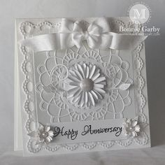 "I started with a white 5-1/2"" square card base.  I then cut 4 pieces of the Ankara Lace Border.  I cut the ends of each piece at a 45 degree angle to form a frame.  I then topped that with a 4-1/4"" square of white shimmer paper backed with some white mulberry paper.  On top of that sits the Felicity Doily which is topped with mini fanciful flourishes and a beautiful Shasta Daisy."