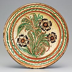 Artist: Unknown. Probably made during Gottfried Aust's tenure as master of the pottery. Image title or type, and date: Dish. Lead-glazed earthenware. 1775–1785. Origin: Salem, North Carolina Medium and size: Lead-glazed earthenware. Diam. 13-3/4 in.  Present location: Collection of Old Salem Museums & Gardens. Source: http://www.antiquesandfineart.com