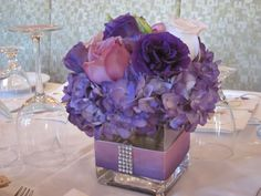 Low Centerpiece - square vase - wrapped with ribbon & diamond accent - purple hydrangeas, purple lisianthus, purple roses and light pink roses