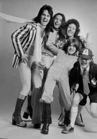 AC/DC's first photo shoot in 1974 Ak! Before Bon Scott joined the brothers Angus and Malcolm Young to record some of the heaviest and grittiest hard rock albums ever pressed into vinyl, AC/DC (with scarf wearing lead singer Dave Evans) had a taste for the sound and fashion of the era : glam!