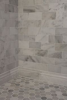 Large gray and white marble subway tile on shower wall and baseboard with a hexagon pattern on the floor. Large gray and white marble subway tile on shower wall and baseboard with a hexagon pattern on the floor.