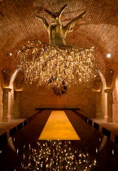 "This elegant chandelier, designed to look like a huge vine loaded 1500 crystals ""grapes"", was designed by Donald Lipski and Jonquil LeMaster. This sculptor-artist duo created the chandelier for the vineyard Kathryn Hall, a wine producer in Rutherford, California. The chandelier is called: ""Chili Red"". It is suspended in the cellars of the vineyard and is part of a sumptuous hall used to receive guests for wine tasting. Related articles : 60-ies Teapot Chandelier ""Deli..."